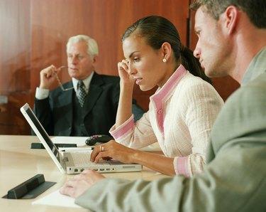 Businesswoman using laptop in boardroom meeting