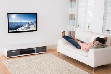 African Woman Lying On Sofa Watching Television