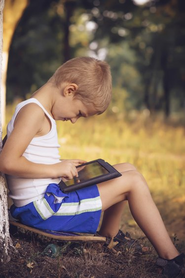 Boy Child playing with Tablet PC Outdoor