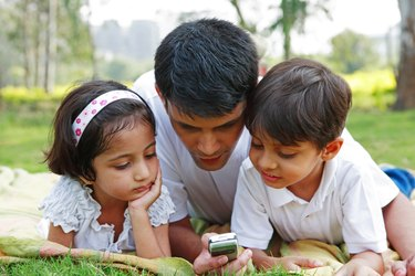 Father showing his mobile to his children