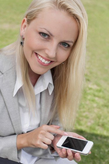 Portrait of happy young businesswoman using smart phone in lawn