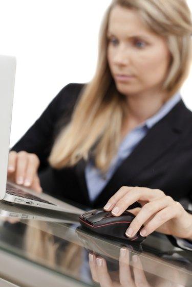 Beautiful young businesswoman using laptop