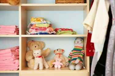 Stuffed animals, clothing and towels on shelves in closet