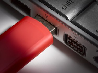 Red USB flash hard drive plugged into laptop, close-up