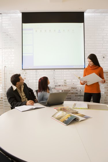 Business people looking at projection screen in conference room