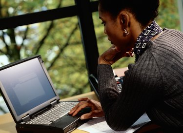 Businesswoman working on laptop, side view