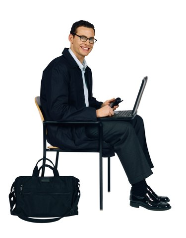 Businessman sitting on chair with laptop computer and cell phone