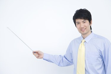 Portrait of businessman holding pointer stick, China, Beijing