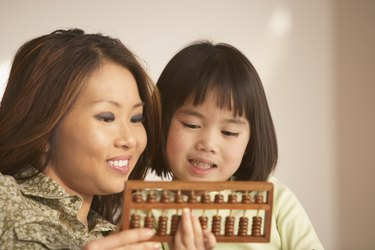 Mother and daughter using an abacus together