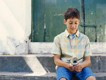 Boy (6-9) using mobile phone