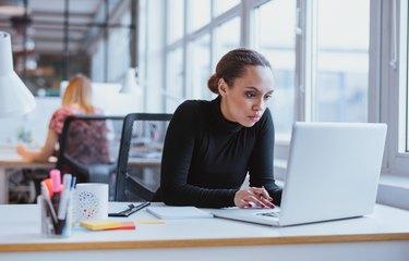 Young business executive using laptop