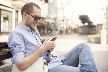 Young man using smartphone of street
