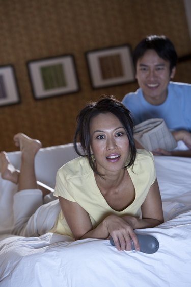 couple wating TV in bed