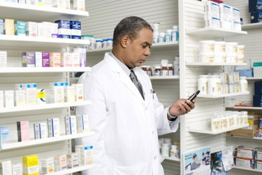Pharmacist checking portable communication device