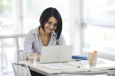 Portrait of a working businesswoman sitting at her desk