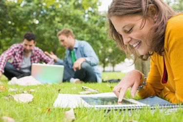 Student using tablet PC while males using laptop in park