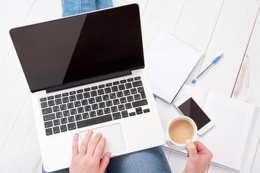 woman  working at home at laptop with  cup of coffee