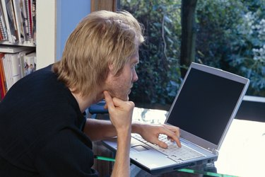 Man using laptop computer in his home office