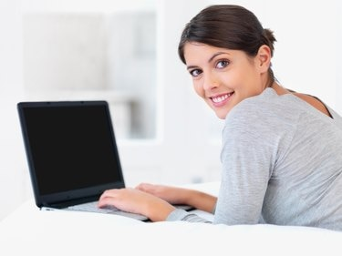 Young woman smiling in bed with a laptop
