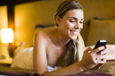 Woman text messaging on a mobile phone in a hotel room, Papeete, Tahiti, French Polynesia