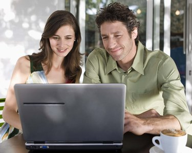 Couple using laptop computer in coffee shop