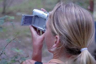 Rear view of a girl using a home video camera
