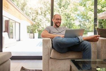 Happy mature man having video call on laptop