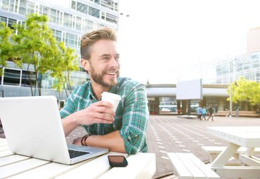 Smiling man sitting outside with laptop and coffee