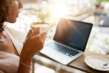 Woman drinking coffee with a laptop at restaurant