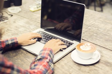 woman typing on a laptop with cup of coffee