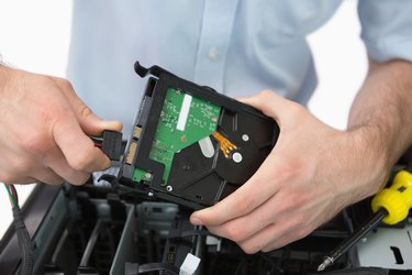 Hands fixing cable to hard disk