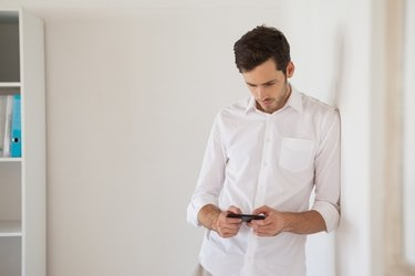 Casual businessman leaning against wall sending a text