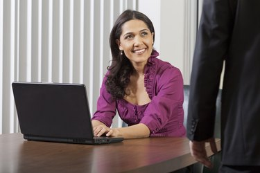 Businesswoman smiling at her boss in office