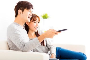 happy young couple watching tv in living room
