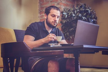 Businessman Using Laptop at Office Coffee Bar