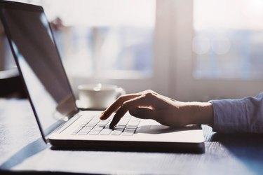 Human hand on laptop keyboard