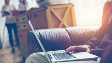 Man with laptop on leather sofa
