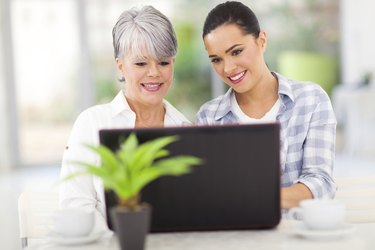 senior mother and daughter using laptop computer