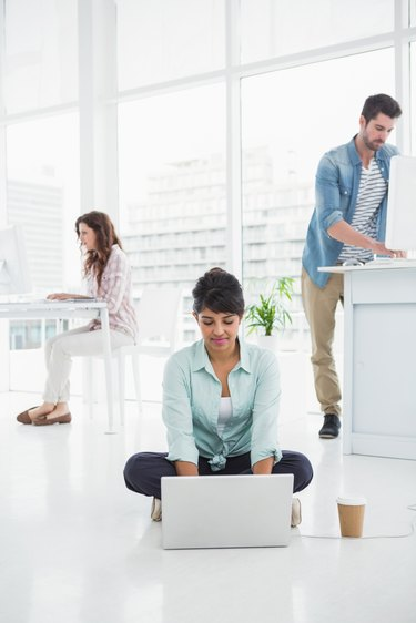 Casual businesswoman sitting on the floor using laptop