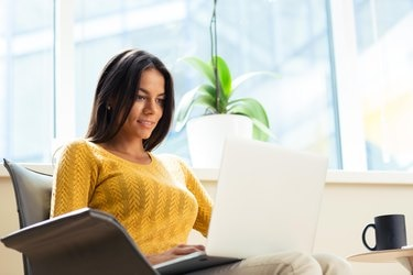 Casual businesswoman sitting on office chair with laptop