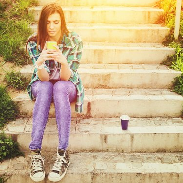 Teenage girl with smartphone and takeaway coffee texting