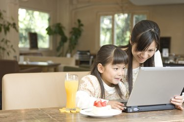 Mother and daughter using laptop at a cafe