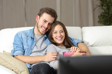 Happy couple watching movie on tv