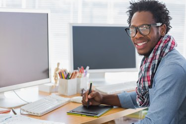 Smiling graphic designer using a graphics tablet