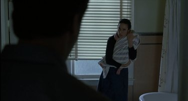 Still of Alicia Nash clutching her baby and confronting John Nash in A Beautiful Mind.