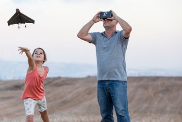 Photo of a father watching on as his daughter launches the PowerUp FPV Paper Airplane VR Drone into the air.