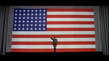 Still of General George S. Patton saluting in front of the United States flag.