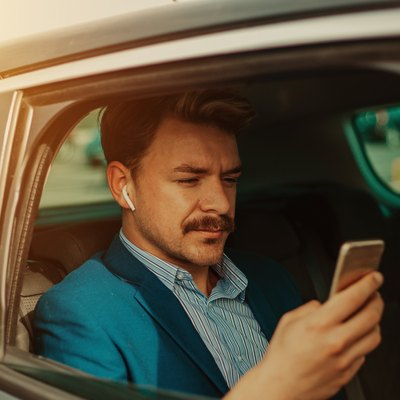Businessman in the car texting