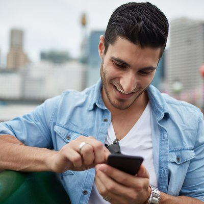 Young millennial man using smart phone in city