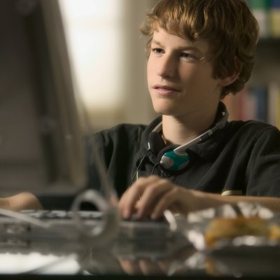 lifestyle portrait of a teenage male as he sits at his computer and works